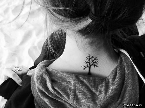 Тату у основания шеи девушки дерево